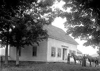 Man and Woman holding horses outside a house.